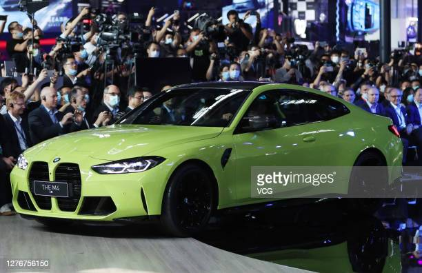 People watch as the new BMW M4 sports car is on display during 2020 Beijing International Automotive Exhibition at China International Exhibition...