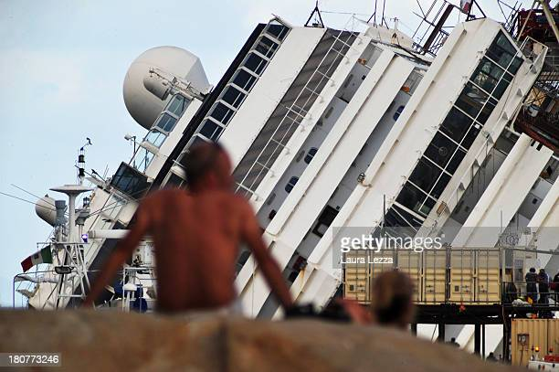 People watch as the parbuckling project to raise the stricken Costa Concordia continues on September 16 2013 in Isola del Giglio Italy Work begins...