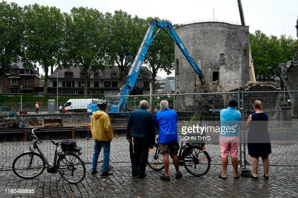 "People watch as the ""Pont des Trous"" medieval bridge is being demolished by a crane in Tournai, where the Scheldt river will be enlarged to allow..."
