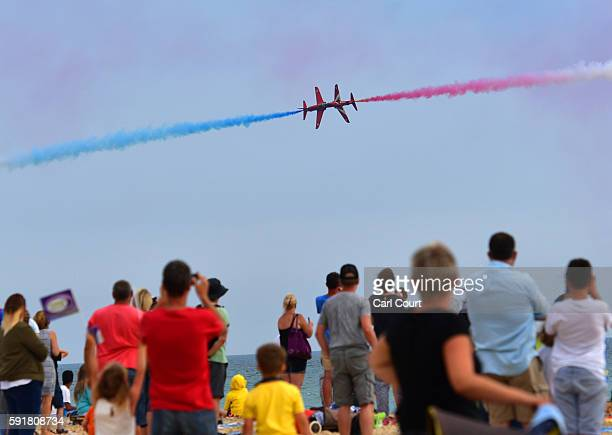 People watch as the Red Arrows aerobatics display team perform during the Bournemouth Air Festival on August 18 2016 in Bournemouth England The air...