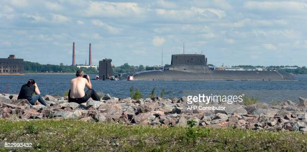 People watch as the Russian submarine Dmitry Donskoy the world's largest in active service arrives at Kronstadt Navy base outside Saint Petersburg on...