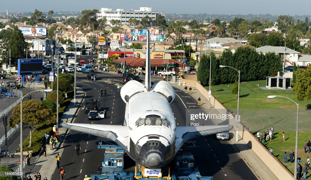 People watch as the Space Shuttle Endeavour arrives at the Forum enroute to the California Science Center on October 13, 2012 in Inglewood, California. Endeavour is on its last mission - a 12-mile creep through city streets, past an eclectic mix of strip malls, mom-and-pop shops, tidy lawns and faded apartment buildings. Its final destination is the California Science Center in South Los Angeles where it will be put on display. NASA's Space Shuttle Program ended in 2011 after 30 years and 135 missions.
