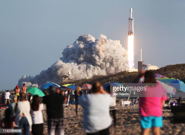 People watch as the SpaceX Falcon Heavy rocket lifts off from launch pad 39A at NASA's Kennedy Space Center on April 11, 2019 in Titusville, Florida....
