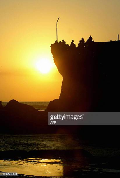 People watch as the sun set at Tanah Lot, Tabanan on the island of Bali, 29 September 2006, prior to the performance of the traditional sacred...