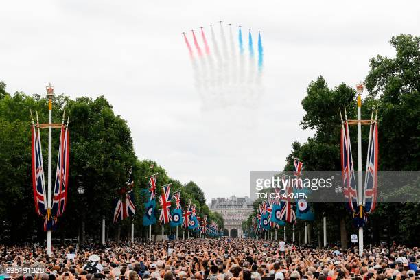 People watch as the The Red Arrows take part in a flypast over the Mall and Buckingham Palace in London on July 10 2018 to mark the centenary of the...