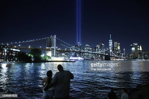 People watch as the Tribute In Light shines into the sky from Lower Manhattan during a test on September 07, 2021 as seen from the Brooklyn borough...