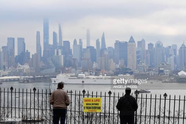 People watch as the USNS Comfort medical ship moves up the Hudson River as it arrives on March 30 2020 in New York as seen from Weehawken New Jersey...