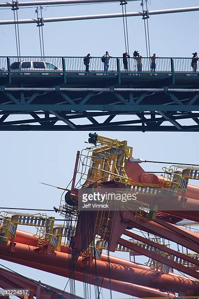 People watch as three of the world's largest Super PostPanamax Cranes pass under the Lions Gate bridge April 27 2005 in Vancouver Canada The cranes...
