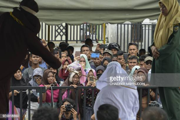 TOPSHOT People watch as Tjia Nyuk Hwa an Indonesian Christian is publicly flogged outside a mosque in Banda Aceh on February 27 for playing a...
