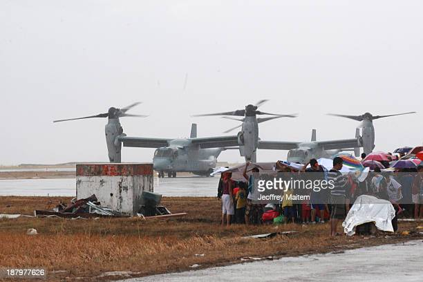 People watch as US Bell Boeing V22 Osprey arrive at the airport to transport humanitarian workers to typhoon affected areas on November 14 2013 in...