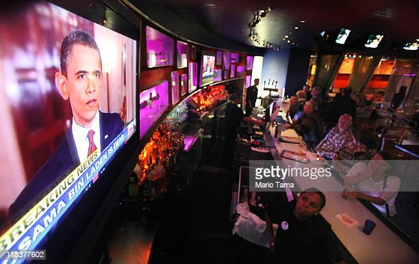 People watch as US President Barack Obama speaks on television at the Planet Hollywood Times Square about the death of accused 911 mastermind Osama...