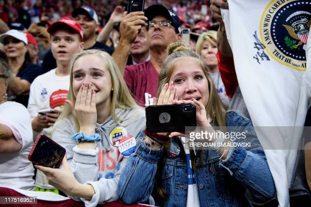 """People watch as US President Donald Trump arrives for a """"Keep America Great"""" rally at the Target Center in Minneapolis, Minnesota on October 10, 2019."""