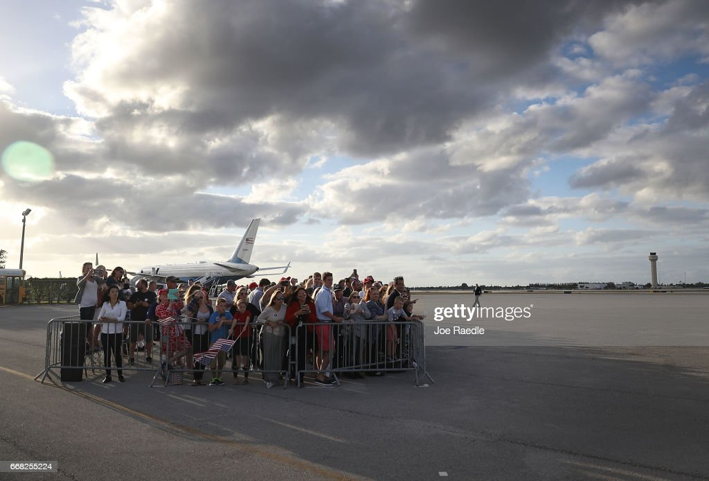 People watch as US President Donald Trump arrives on Air Force One at the Palm Beach International Airport to spend Easter weekend at Mar-a-Lago resort on April 13, 2017 in West Palm Beach, Florida. President Trump has made numerous trips to his Florida home and according to reports has cost over an estimated $20 million in his first 80 days in office.