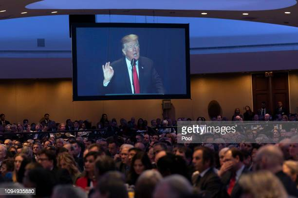 People watch as US President Donald Trump speaks during the 2019 National Prayer Breakfast on February 7 2019 in Washington DC In his speech Trump...