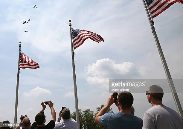 People watch as vintage World War II war planes fliy in the missing man formation down the National Mall May 8 2015 in Washington DC Fifty six...