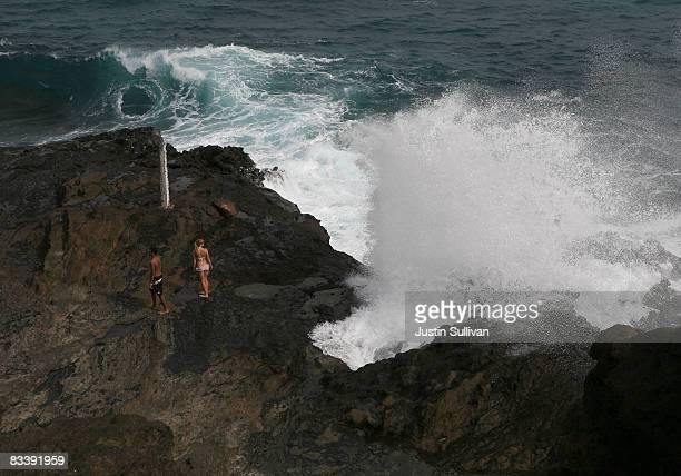 People watch as water shoots out of the Halona Blowhole October 22 2008 in Honolulu Hawaii Democratic presidential candidate Barack Obama has...