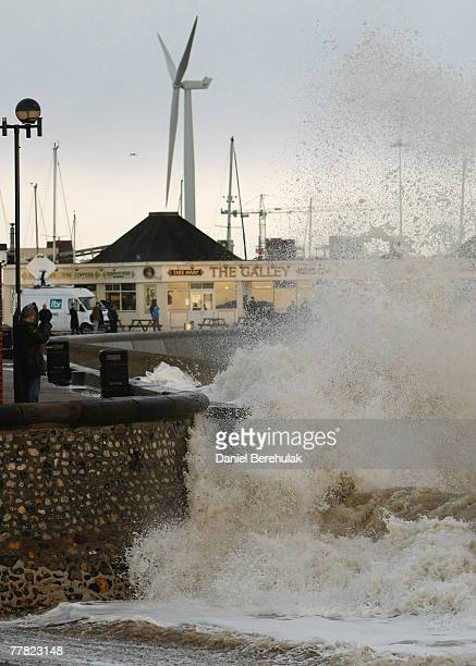 People watch as waves crash into the sea wall at Lowestoft on November 9 2007 near Great Yarmouth United Kingdom The fear of widespread flooding in...
