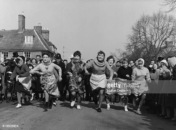 People watch as women take part in a pancake race at Onley