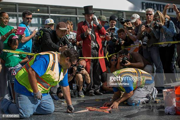 People watch as workers repair the Hollywood Walk of Fame star of Republican presidential candidate Donald Trump after it was vandalized by a...