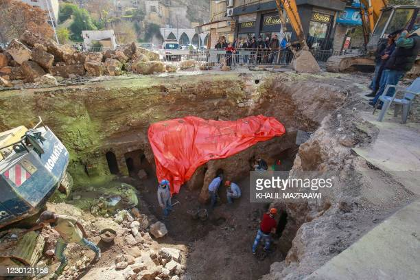 People watch as workers uncover the ruins of a recently discovered Roman archaeological site in the Jordanian capital Amman, on December 14, 2020. -...