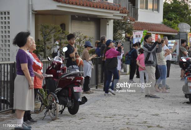 People watch as World Heritage site Shuri Castle burns down in Naha the capital of Japan's Okinawa Prefecture on Oct 31 2019