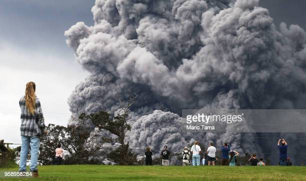People watch at a golf course as an ash plume rises in the distance from the Kilauea volcano on Hawaii's Big Island on May 15 2018 in Hawaii...