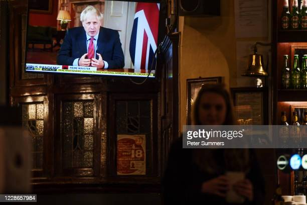People watch British Prime Minister Boris Johnson making a televised address to the nation inside the Westminster Arms pub on September 22, 2020 in...