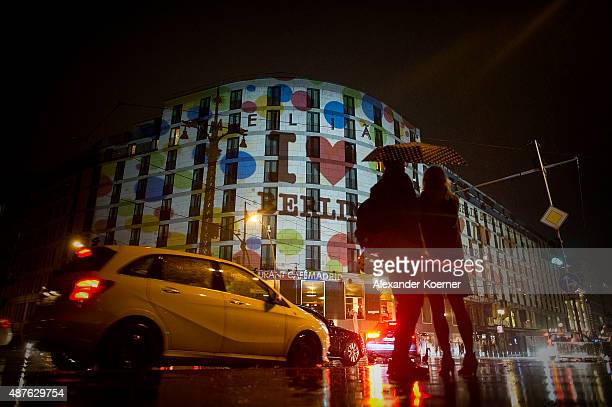 People watch buildings along the river Spree in downtown Berlin which are illuminated to celebrate the 20th jubilee of eBay on September 10 2015 in...