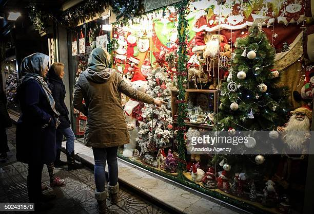 People watch Christmas store at Mirzayeh Shirazi district where mostly Armenian people live in Tehran Iran on December 24 2015