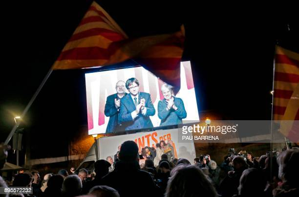 People watch deposed Catalan regional president and 'Junts per Catalonia' JUNTSXCAT grouping candidate Carles Puigdemont speaking via videoconference...