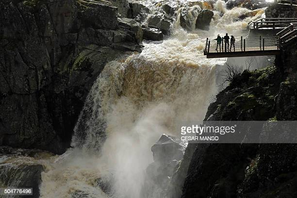 People watch El Pozo de los Humos waterfall from a scenery viewpoint near Masueco in the province of Salamanca on January 13 2016 Heavy rains in...
