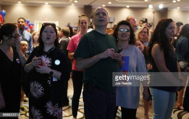 People watch election results come in on a television screen setup at the election party for Democratic candidate Jon Ossoff being held at the Westin...