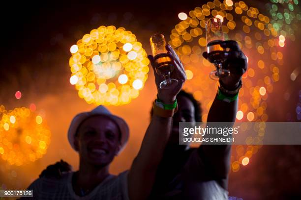 People watch fireworks during New Years celebrations at Copacabana beach in Rio de Janeiro on January 1 2018 / AFP PHOTO / DOUGLAS SHINEIDR