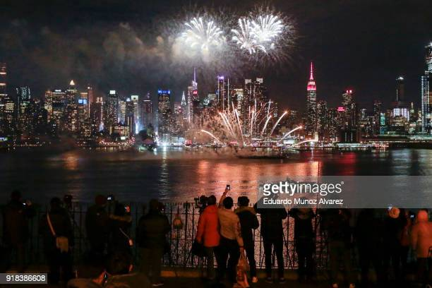 People watch fireworks explode over the Hudson River against the backdrop of Manhattan marking Chinese New Year celebrations on February 14 2018 in...