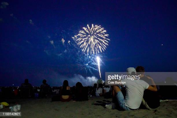 People watch fireworks fly over Ashbridges Bay during Canada Day festivities on July 1 2019 in Toronto Canada Canada Day commemorates the July 1 1867...