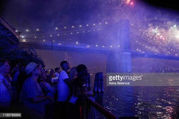 People watch fireworks light up the Brooklyn Bridge during the annual Macy's fireworks show on the East River from Manhattan July 4 2019 in New York...