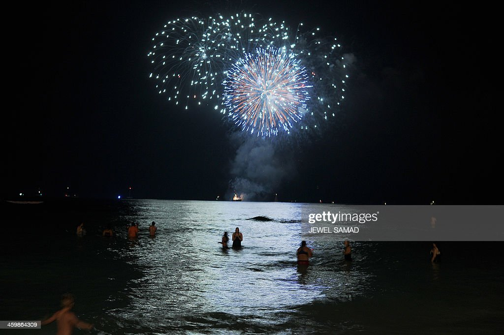 People watch fireworks lighting up the sky over Waikiki beach in Honolulu, Hawaii, early on January 1, 2014. People around the world are celebrating the New Year of 2014. AFP PHOTO/Jewel SAMAD
