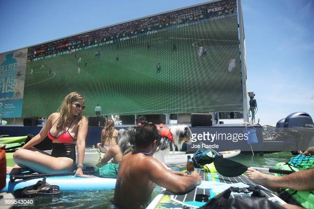 People watch France playing against Croatia in the World Cup final as it is being broadcast from the Ballyhoo Media boat setup in the Intracoastal...
