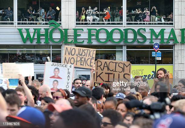 People watch from a Whole Foods store as protesters gather at a rally honoring Trayvon Martin at Union Square in Manhattan on July 14 2013 in New...