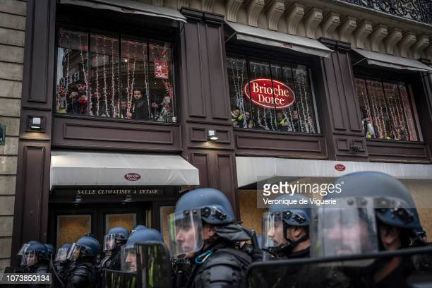 People watch from a window as Police clash the Yellow Vests at Opera on December 15 2018 in Paris France The protesters gathered in Paris for a 5th...