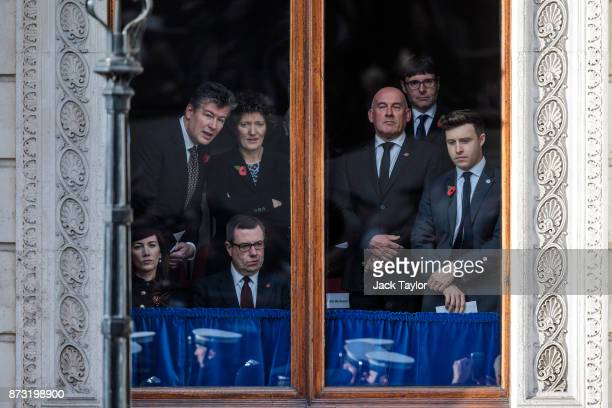 People watch from a window on Whitehall as the Remembrance Sunday memorial is held around the Cenotaph on November 12 2017 in London England The...