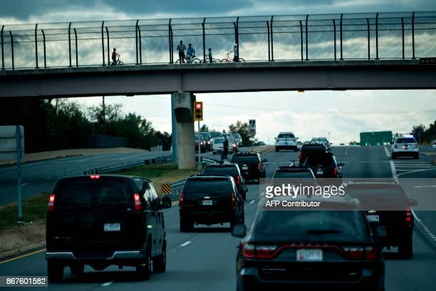 People watch from an overpass as a motorcade with US President Donald Trump drives after departing Trump National Golf Course October 28 2017 in...