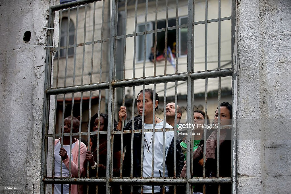 People watch from behind a gate as Pope Francis speaks in the Varghina favela, or shantytown, on July 25, 2013 in Rio de Janeiro, Brazil. More than 1.5 million pilgrims are expected to join Pope Francis for his visit to the Catholic Church's World Youth Day celebrations. Pope Francis will deliver his welcome address to the celebrations on Copacabana Beach later today as World Youth Day runs July 23-28.