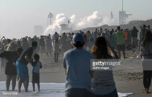 People watch from Playalinda Beach at Canaveral National Seashore as a cloud of smoke forms when a SpaceX Falcon 9 rocket carrying 60 Starlink...