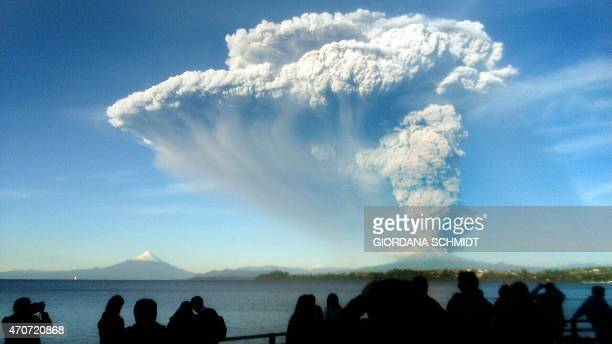 People watch from Puerto Varas, southern Chile, a high column of ash and lava spewing from the Calbuco volcano, on April 22, 2015. Chile's Calbuco...