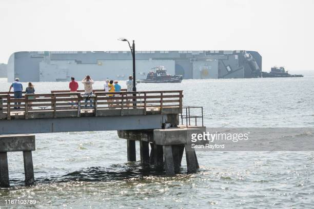 People watch from St. Simons Pier as emergency responders work to rescue crew members from a capsized cargo ship on September 9, 2019 in St Simons...