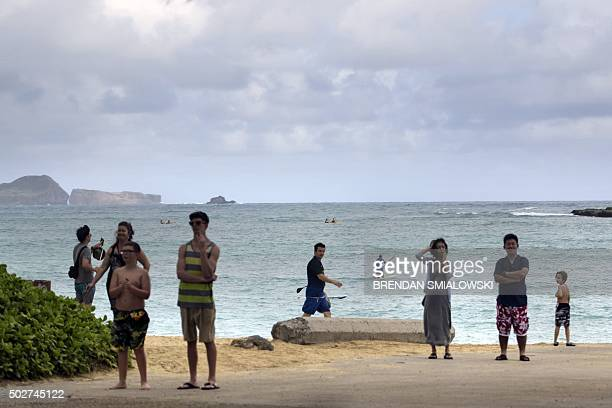 People watch from the beach as a motorcade with US President Barack Obama travels to the Mid-Pacific Country Club golf course December 28, 2015 in...