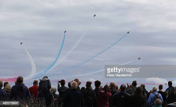 People watch from the beach as the RAF Red Arrows display team takes part in the Clacton Airshow on August 27 2015 in ClactononSea England This is...