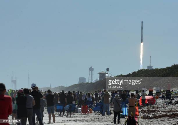 People watch from the beach at Canaveral National Seashore as a SpaceX Falcon 9 rocket with the Dragon spacecraft launches from pad 39A at the...