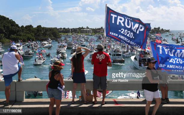 People watch from the bridge as boaters show their support for President Donald Trump at the start to a parade down the Intracoastal Waterway to just...